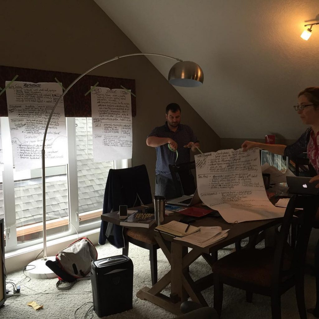 A man and a woman taping flipchart paper covered in writing above tall windows, which are to the left.