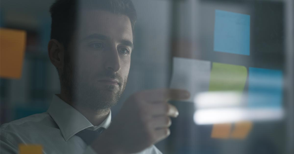 A manager stares at his workplan, figuring out how to redistribute the project.